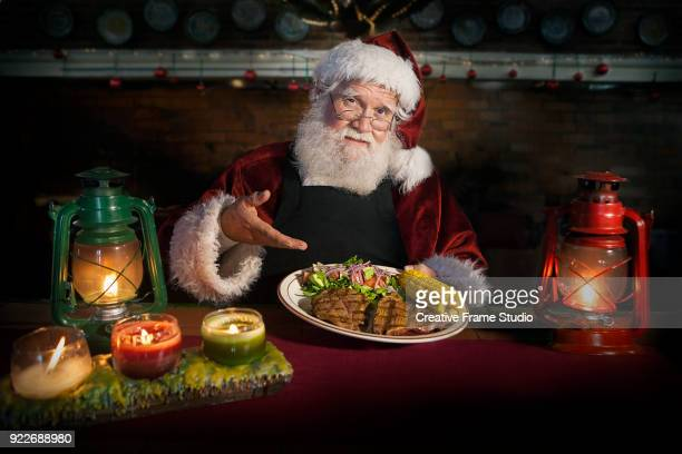 chef santa claus holding a delicious grilled steak dish accompanied with corn and salad in a cozy kitchen counter lit by a candles and oil lamps - steakhouse stock photos and pictures