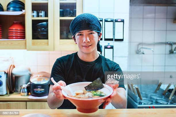 Chef serving a bowl of freshly made ramen