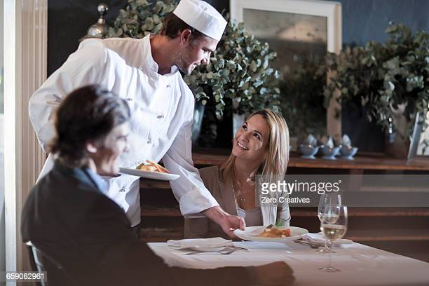 Chef serving customer in restaurant