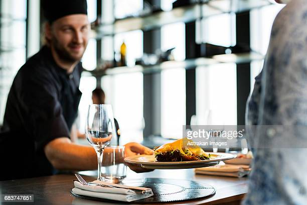 Chef serving dish to customer at sky bar restaurant