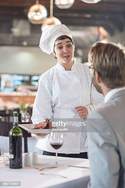 Chef serving food for businessman