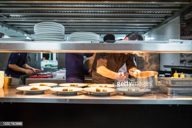 chef serving food in restaurant - commercial kitchen stock pictures, royalty-free photos & images