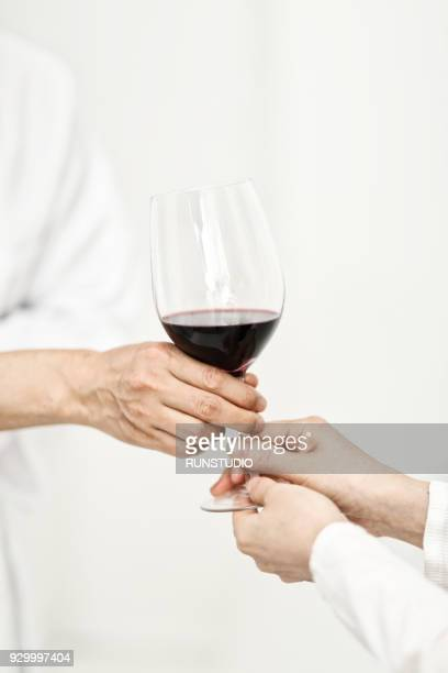 Chef serving glass of wine for woman