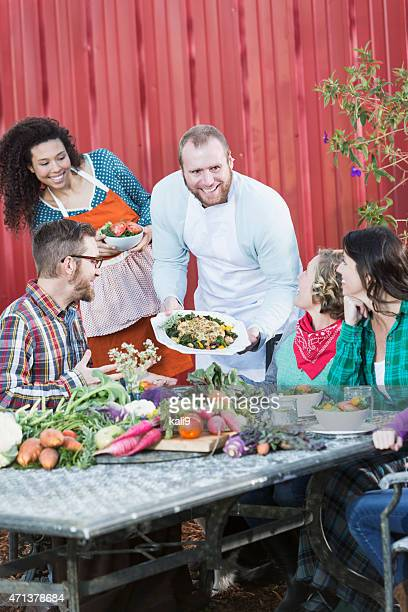 chef serving locally grown food to group of people - farm to table stock photos and pictures