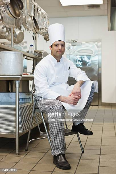 Chef sitting on stool in kitchen