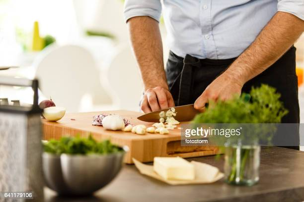 Chef slicing garlic on cutting board