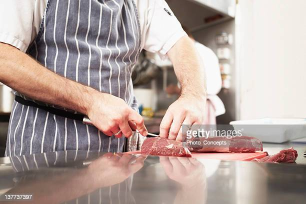 Chef slicing meat in kitchen