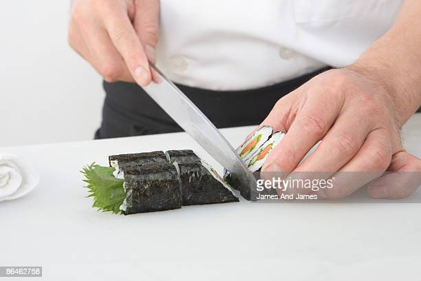 Chef slicing sushi roll