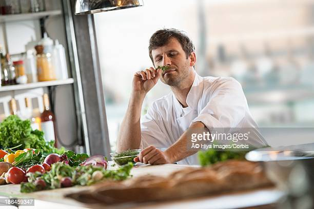 Chef smelling vegetables in kitchen