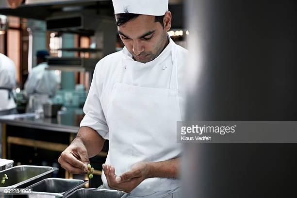 chef sorting out peas in kitchen - uniform stock-fotos und bilder