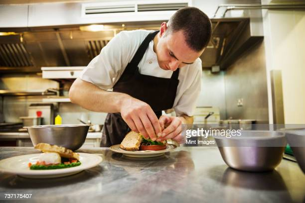 Chef standing in kitchen, wearing apron, plating food.