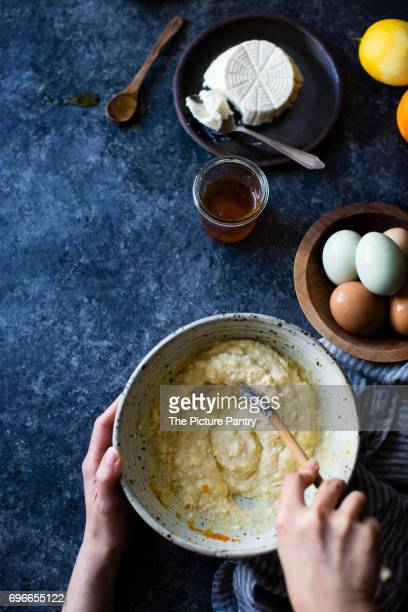 A chef stiring ingredients in a mixing bowl. Ingredients include rocotta, eggs and honey.