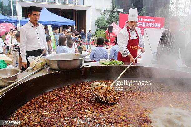 A chef stirs food in a 315 meters diameter hotpot at the intersection of Zhengbian Road and Jianye Road during the 3rd Zhengzhou Hotpot Festival on...