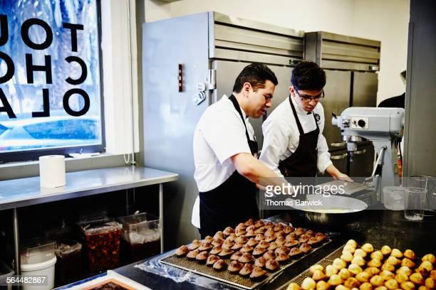 Chef supervising as baker prepares glaze