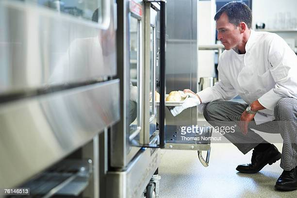 Chef taking food from oven in restaurant kitchen