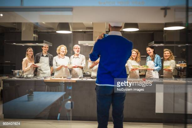 Chef taking photograph of  attendees of cooking class