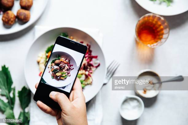 chef taking photograph of vegan falafel bowl on table. - photo messaging stock pictures, royalty-free photos & images
