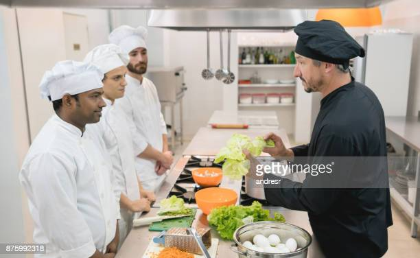 Chef teacher showing a fresh lettuce to his students and everyone paying attention