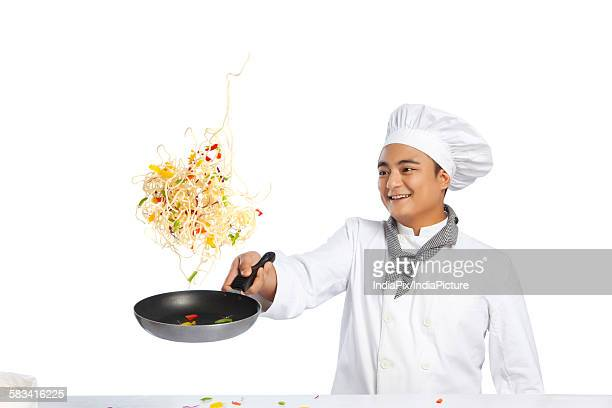 Chef tossing food in frying pan