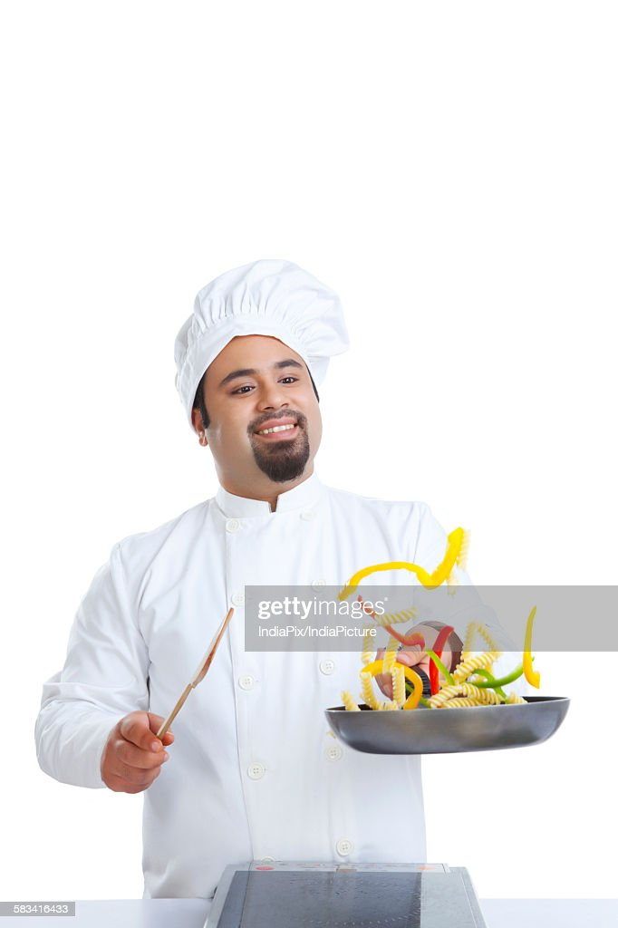 Chef tossing food in pan : Stock Photo