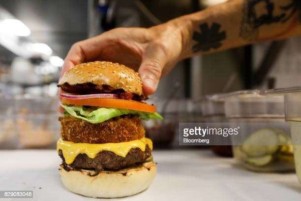 Chef with Gourmet Burger Kitchen Ltd. Delivery-only kitchen, places the top of a bun on a burger at a Deliveroo Editions field kitchen, operated by...