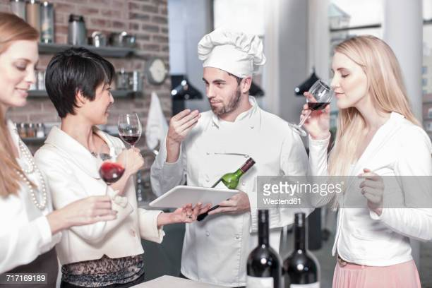 Chef with three women tasting red wine in kitchen