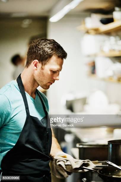 Chef working at stove in restaurant kitchen