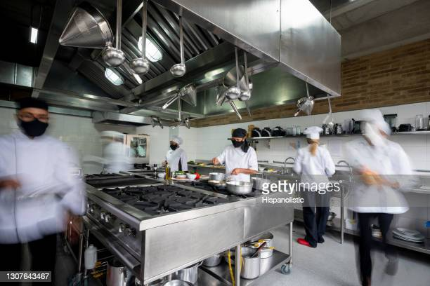chef working in a kitchen wearing facemask during the pandemic - blurred motion effect - catering building stock pictures, royalty-free photos & images