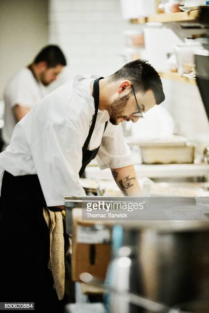 Chef working on dinner preparation in restaurant kitchen
