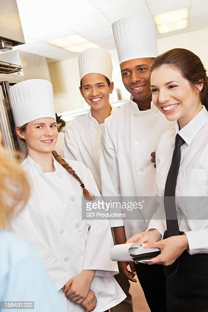 Köche und Kellnerin hören restaurant manager in der Küche