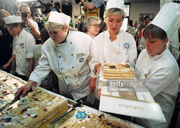 Chef''s at the Slavyanskaya hotel cut a giant cake into pieces, to be sold at an equivalent of seven dollars a serving, June 21 2001 in Moscow,...