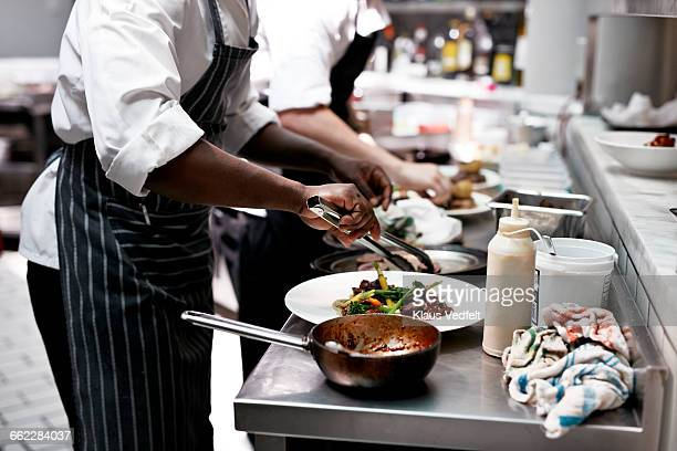 Chefs finishing dishes in kitchen at restaurant