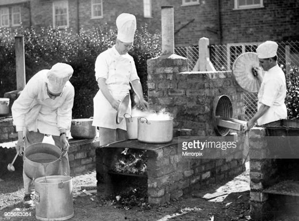 Chefs from Liverpool Education Committee School prepare a meal in a field kitchen using a bin as an improvised oven 23rd September 1952 Pictured...