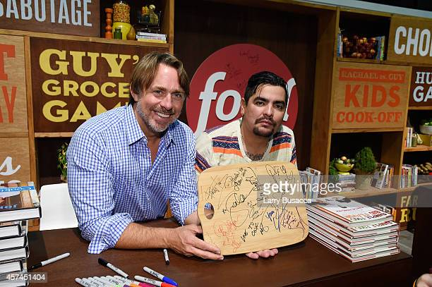 Chefs John Besh and Aaron Sanchez sign copies of their books at the Grand Tasting presented by ShopRite featuring KitchenAid® culinary demonstrations...