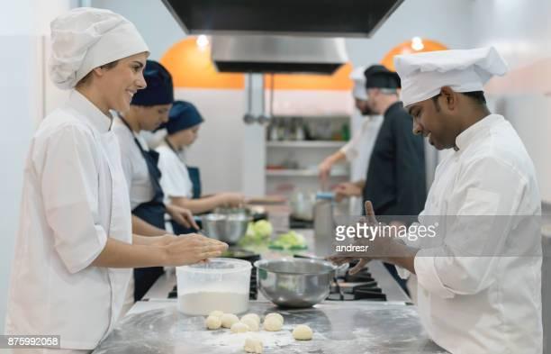 Köche, Kneten von Teig backen Brot suchen glücklich und lächelnd