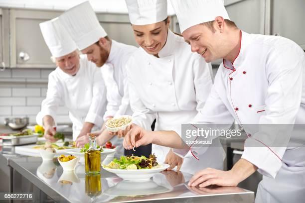 Chefs making salad in restaurant kitchen