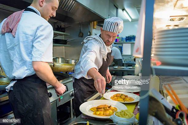 Chefs plating up lobster ravioli in traditional Italian restaurant kitchen
