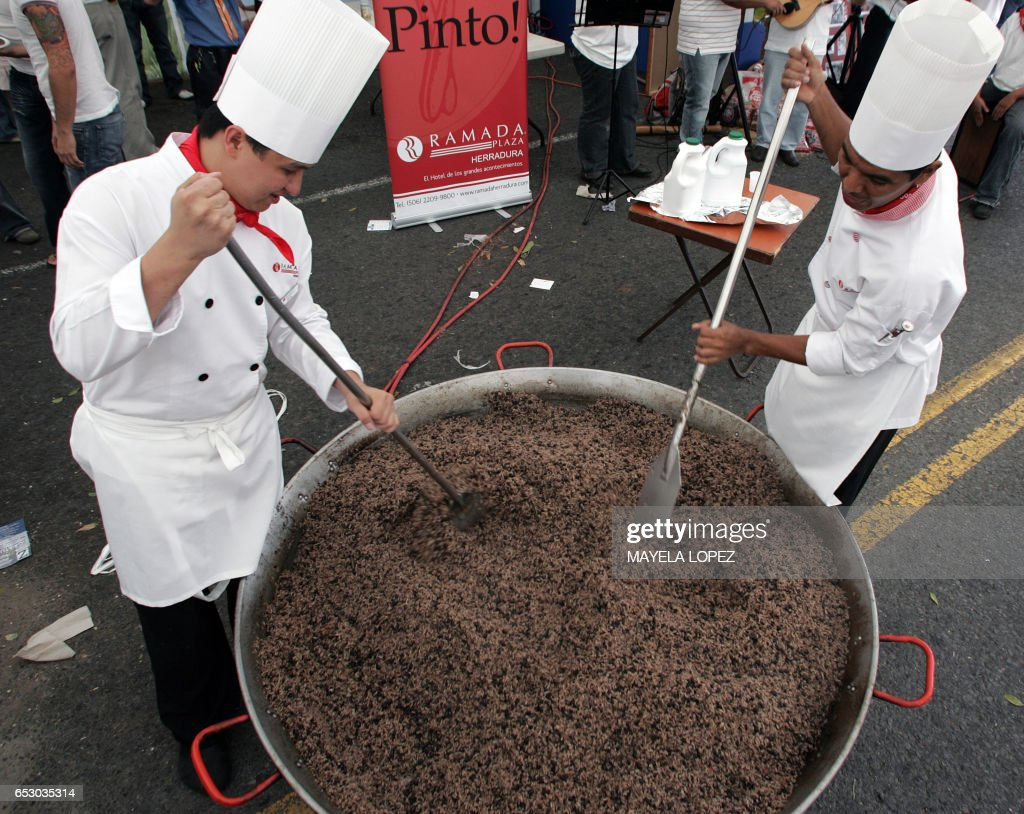 Chefs prepare a big casserole of 'Gallo Pinto' -typical dish made of rice and beans- on April 13, 2008, in one of the main streets of San Jose during the first Gallo Pinto National Festival. About 80 people worked to make a giant Gallo Pinto that was shared out between over 30 thousand people. AFP PHOTO/ Mayela LOPEZ /