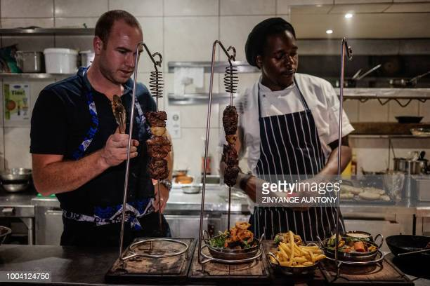 Chefs prepare food at a restaurant on June 28 2018 in the resort town of Victoria Falls After nearly two decades in the doldrums Zimbabwe's tourism...