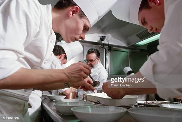 Chefs Prepare Food at Restaurant Alain Ducasse