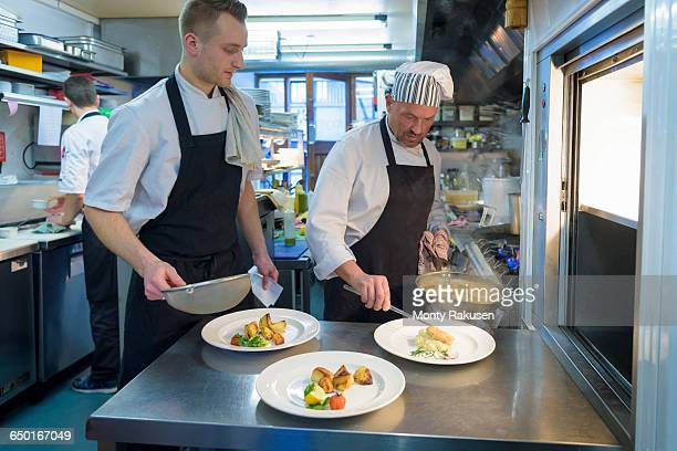 chefs preparing dishes in traditional italian restaurant kitchen - オトレイ ストックフォトと画像