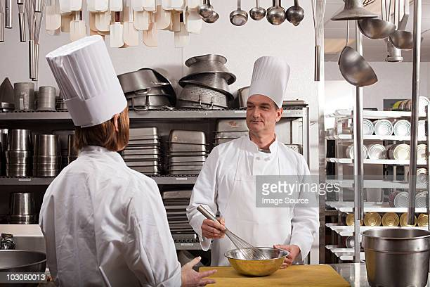 chefs preparing food in commercial kitchen - women whipping men stock photos and pictures