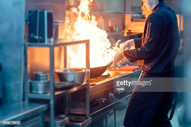 Chefs Preparing Meal In a Wok.
