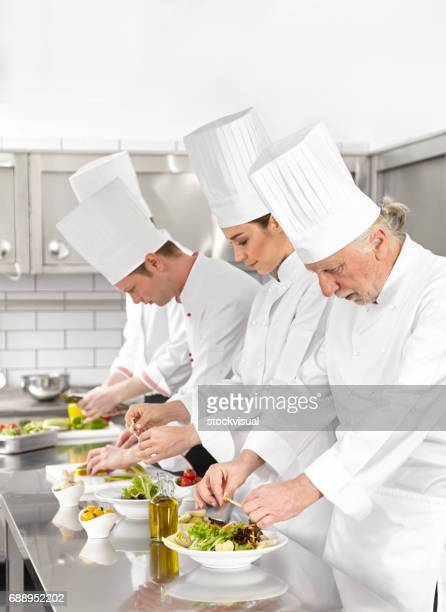 Chefs prepearing salad in commercial kitchen
