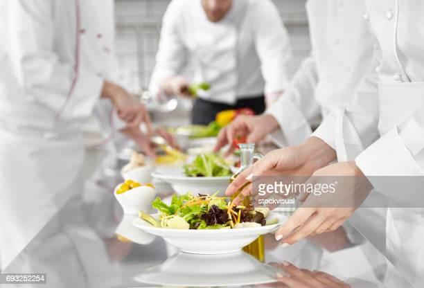 köche prepearing salat in großküchen - gourmet küche stock-fotos und bilder