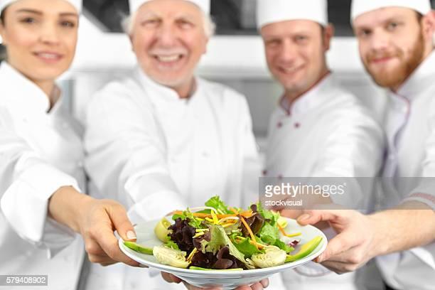 Chefs presenting salad