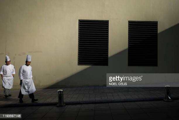 Chefs walk along a sidewalk in Beijing on January 14, 2020. - China's trade surplus with the United States narrowed last year as the world's two...