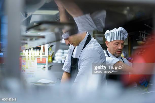 Chefs work in traditional Italian restaurant kitchen