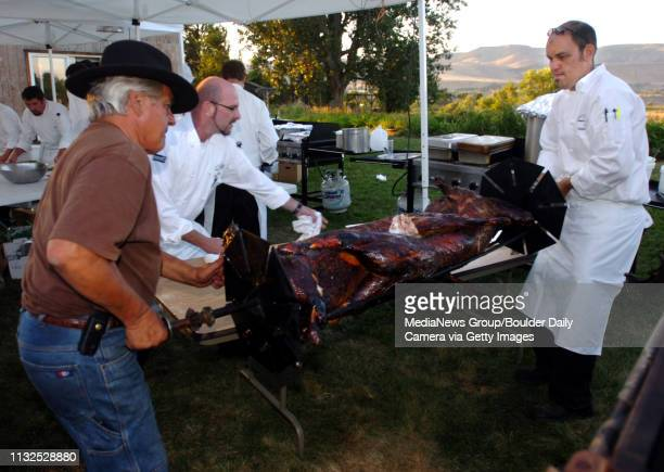 Chefs Yvon Gros, left, Michael Scott, and Adam Dulye, take the cooked lambs out of the roaster.Students from the Culinary School of the Rockies spend...