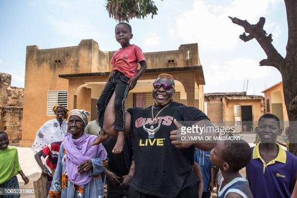 Cheick Ahmed AlHassan Sanou aka Iron Biby lifts a child in the courtyard of his grand mother's home in BoboDioulasso second biggest city of Burkina...